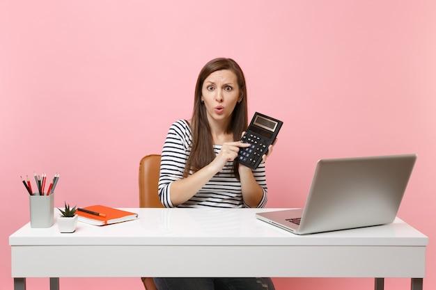 Giovane donna preoccupata che tiene in mano la calcolatrice mentre è seduta, lavorando su un progetto in ufficio con un computer portatile contemporaneo isolato su sfondo rosa pastello. concetto di carriera aziendale di successo. copia spazio.