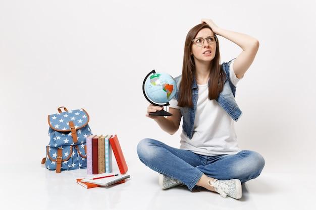 Giovane studentessa preoccupata con gli occhiali che tiene il globo del mondo aggrappato alla testa guardando in alto seduto vicino allo zaino, libri di scuola isolati su muro bianco