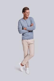 Giovane e sicuro di sé. per tutta la lunghezza del bel giovane che tiene le braccia incrociate e sorride mentre sta in piedi su uno sfondo grigio gray