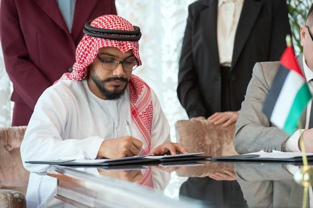 Giovane uomo d'affari arabo fiducioso o delegato in abiti nazionali che firma un contratto di partnership commerciale tra emirati arabi uniti e russia