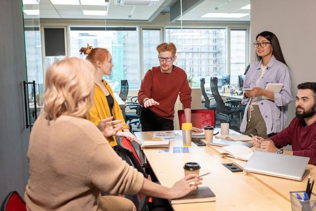 Giovane mediatore fiducioso che discute con uno dei colleghi che spiega il suo punto di vista durante il brainstorming alla riunione di avvio in ufficio