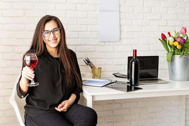 Giovane donna d'affari fiducioso bere vino, celebrando le vacanze di primavera in ufficio