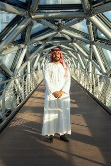 Giovane uomo d'affari o delegato fiducioso in abbigliamento arabo nazionale in piedi davanti alla telecamera su un lungo corridoio all'interno del business center