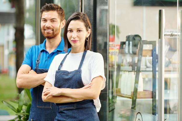 Giovane coppia fiduciosa in piedi all'ingresso di un piccolo coffeeshop che hanno appena aperto