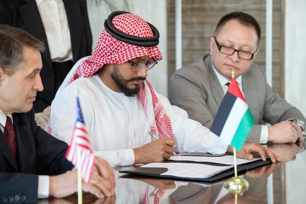 Giovane delegato fiducioso in abiti arabi nazionali che firma un contratto di partnership commerciale tra emirati arabi uniti e stati uniti dopo la negoziazione