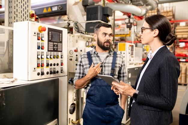 Giovane ingegnere fiducioso della fabbrica di lavorazione dei polimeri che spiega qualcosa al partner commerciale femminile