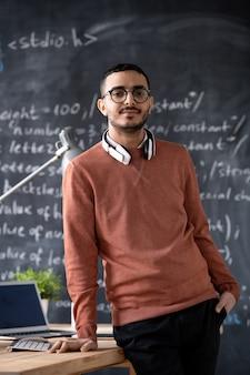 Giovane it-manager fiducioso in abbigliamento casual e occhiali in piedi dalla scrivania con il computer portatile sulla lavagna con la formula