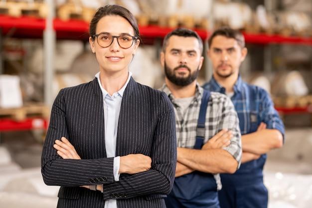 Giovane leader fiducioso della squadra in piedi di fronte a due operai della fabbrica di produzione chimica contemporanea