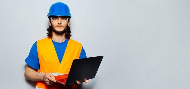 Giovane uomo fiducioso, ingegnere operaio edile che indossa attrezzature di sicurezza, utilizzando laptop su sfondo grigio. vista panoramica del banner con spazio di copia.