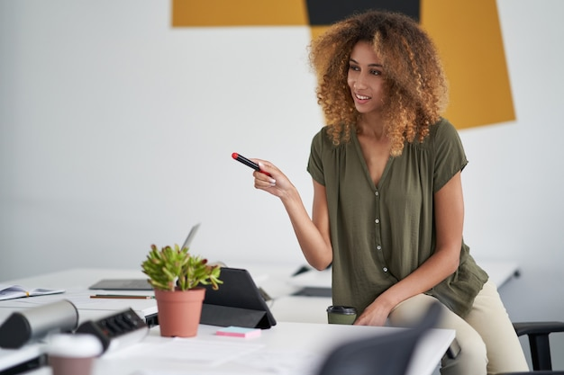 Giovane donna d'affari di razza mista fiduciosa o amministratore delegato femminile seduta sul tavolo con in mano un pennarello e