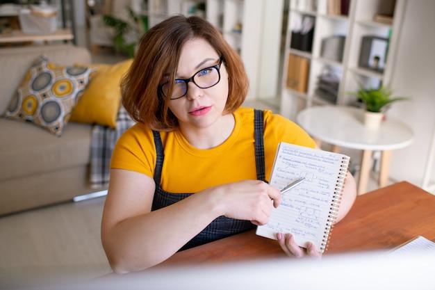 Giovane insegnante fiducioso in abbigliamento casual e occhiali da vista che punta a note chimiche sulla pagina del quaderno mentre consulta lo studente in linea a casa