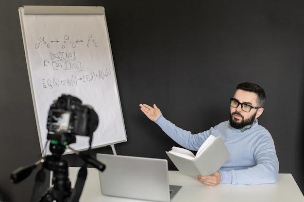 Giovane insegnante fiducioso di chimica che spiega le formule dei suoi studenti sulla lavagna mentre guarda il display del laptop durante la lezione online