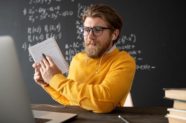 Giovane insegnante fiducioso in occhiali e pullon che punta ai suoi appunti nel quaderno mentre li spiega al pubblico online davanti al computer portatile