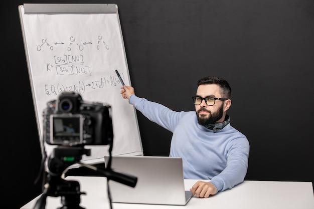 Giovane insegnante fiducioso che indica alla lavagna con formule chimiche durante la lezione online