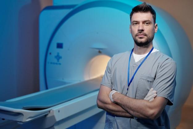 Giovane professionista di tomografia fiducioso che incrocia le braccia per il petto