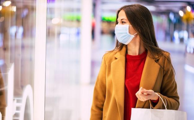 Giovane donna alla moda fiduciosa in una mascherina medica di sicurezza con una borsa della spesa sta camminando nel centro commerciale