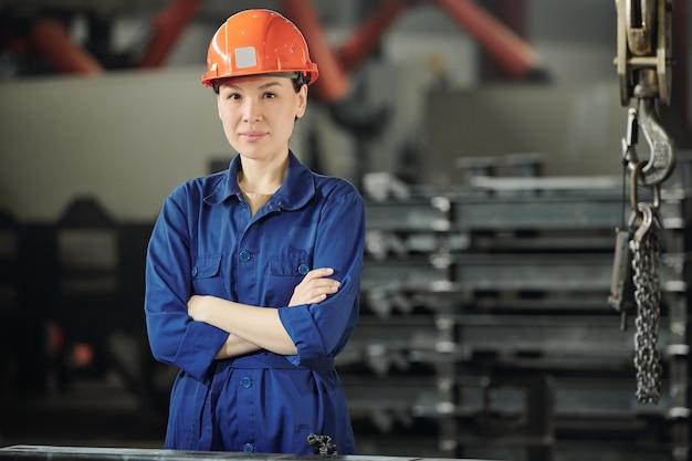 Giovane donna sicura di sé in elmetto protettivo, guanti e indumenti da lavoro blu che attraversano le braccia sul petto