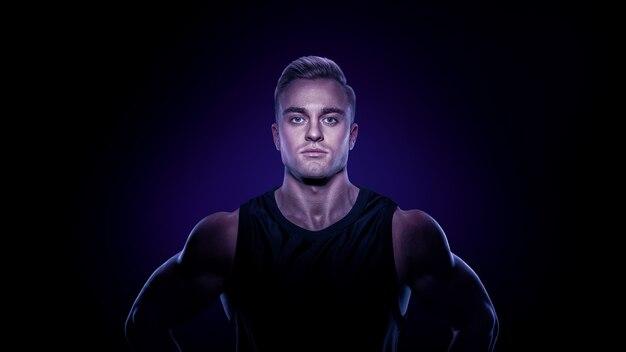 Giovane ragazzo culturista muscolare fiducioso in piedi su sfondo nero e in posa del muscolo bicipite bodybuilding classico