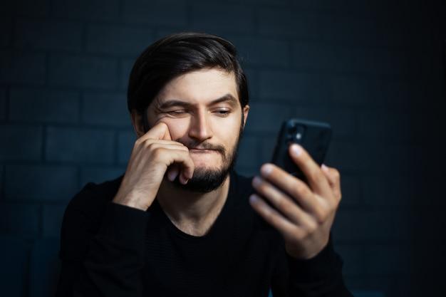 Giovane uomo confuso che guarda nello smartphone sullo sfondo del muro di mattoni nero.