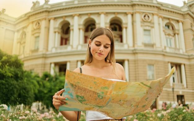 Turista della donna giovane e confusa tiene nelle sue mani la mappa della città