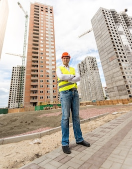 Giovane ingegnere edile davanti a edifici in costruzione