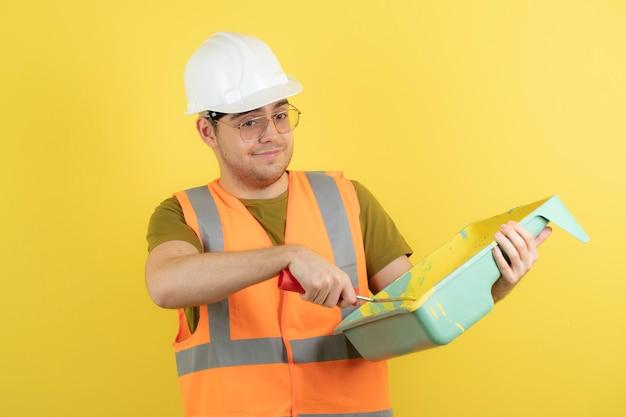 Giovane operaio edile in elmetto protettivo che cattura vernice gialla con rullo di pittura.