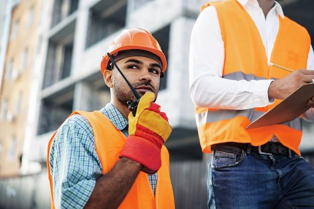 Giovane operaio edile in uniforme utilizzando walkie talkie in loco, primo piano ritratto