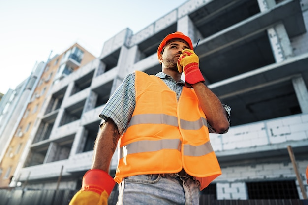 Giovane operaio edile in uniforme che utilizza un walkie-talkie sul posto