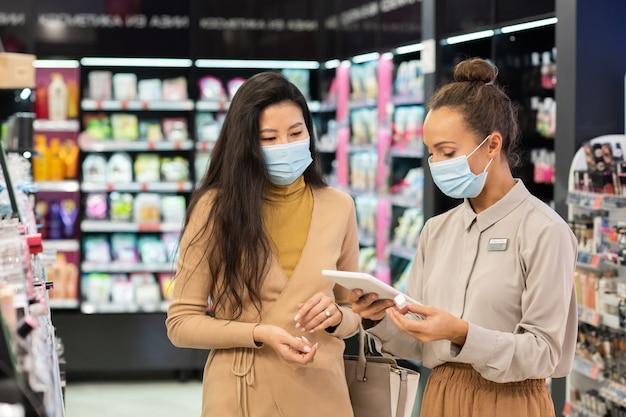 Giovane consulente in maschera protettiva che scorre nel tablet mentre cerca il prezzo del lucidalabbra ricercato da uno dei clienti nel supermercato di bellezza