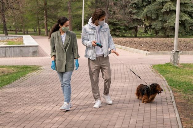 Giovane coppia contemporanea in abbigliamento casual e maschere protettive facendo una passeggiata lungo la strada nel parco pubblico