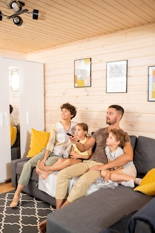 Giovane coppia contemporanea e i loro due simpatici bambini in abbigliamento casual seduti sul divano in soggiorno e guardando il programma tv nel fine settimana