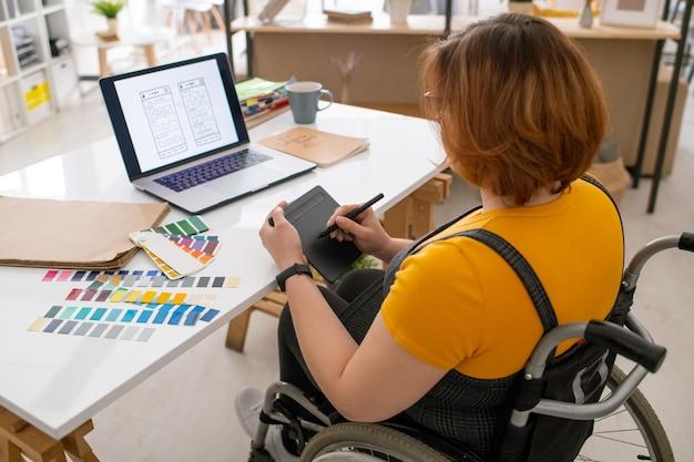 Giovane designer contemporaneo in sedia a rotelle utilizzando tablet con stilo mentre si lavora su nuove tecnologie di comunicazione davanti al computer portatile