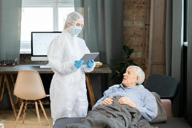 Giovane medico contemporaneo in tute protettive che utilizza tablet per riempire il congedo per malattia elettronico dell'uomo anziano sdraiato sul divano sotto la coperta