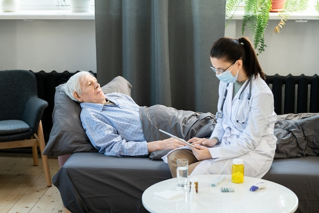 Giovane dottoressa contemporanea in camice bianco che utilizza tablet per riempire il congedo per malattia elettronico dell'uomo anziano sdraiato sul divano sotto la coperta