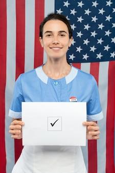 Giovane cameriera sorridente contemporanea in uniforme blu che mostra la sua scheda elettorale con segno di spunta in piazza mentre si trovava contro la bandiera degli stati uniti
