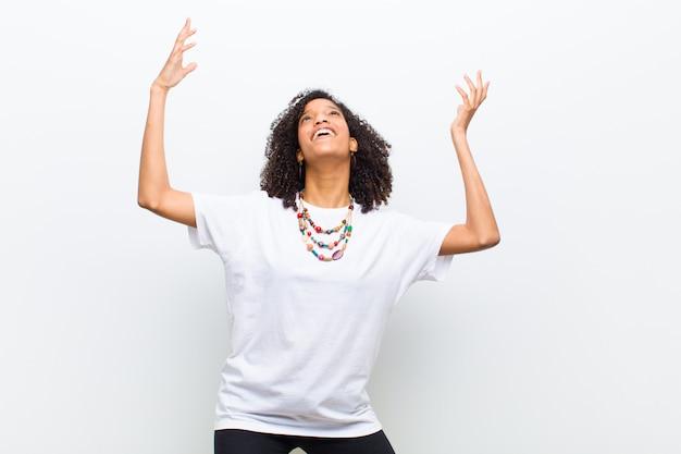Giovane donna afroamericana fresca sentirsi felice, stupita, fortunata e sorpresa, celebrando la vittoria con entrambe le mani in alto