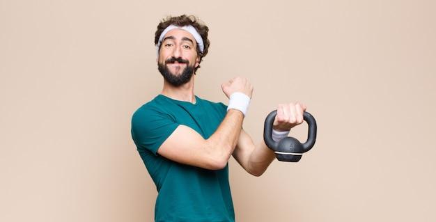 Giovane uomo barbuto freddo in palestra con un manubrio. concetto di sport