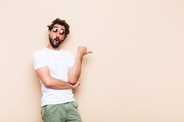 Giovane uomo barbuto fresco sorpreso e indicando il lato
