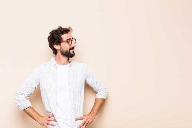Giovane uomo barbuto freddo che pensa o che dubita dell'espressione