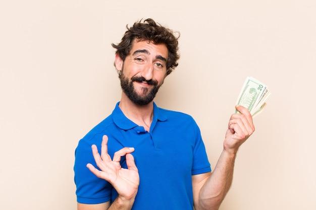 Giovane uomo barbuto fresco con banconote dolar