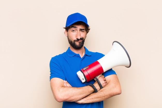 Giovane uomo barbuto freddo con un megafono