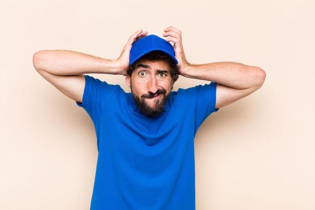 Giovane uomo barbuto freddo con espressione di sorpresa o shock