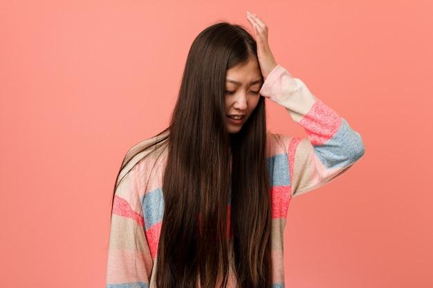 Giovane donna cinese fredda che dimentica qualcosa, schiaffeggiando la fronte con il palmo e chiudendo gli occhi.