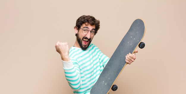 Giovane uomo freddo barbuto con uno skateboard