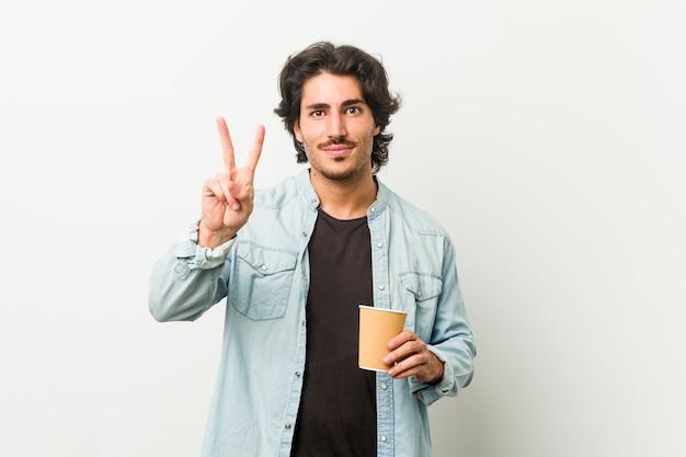 Giovane uomo freddo che beve un caffè che mostra il numero due con le dita.