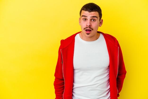 Giovane uomo freddo isolato sulla parete gialla che è scioccato a causa di qualcosa che ha visto