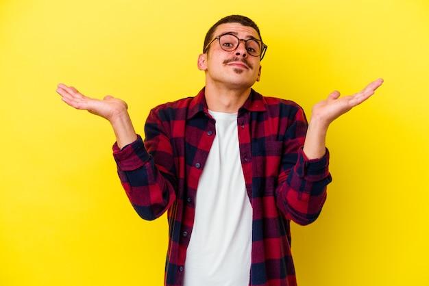 Giovane uomo freddo isolato sul muro giallo confuso e dubbioso scrollare le spalle per tenere uno spazio di copia