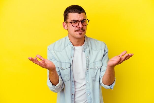 Giovane uomo freddo isolato sulla parete gialla dubitando e alzando le spalle nel gesto interrogativo