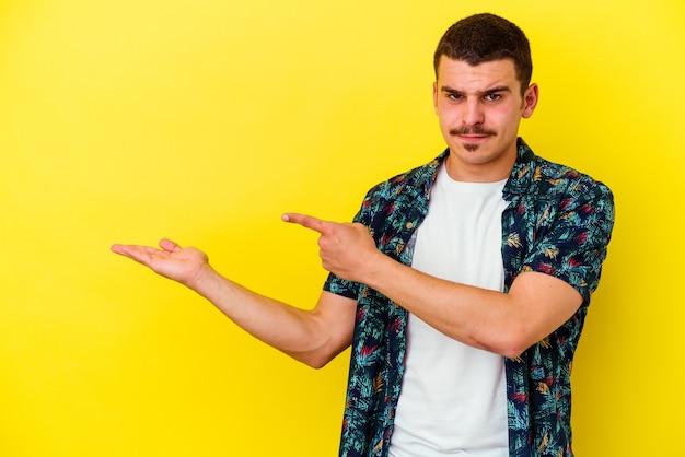 Giovane uomo freddo isolato sulla parete gialla eccitato in possesso di uno spazio di copia sul palmo