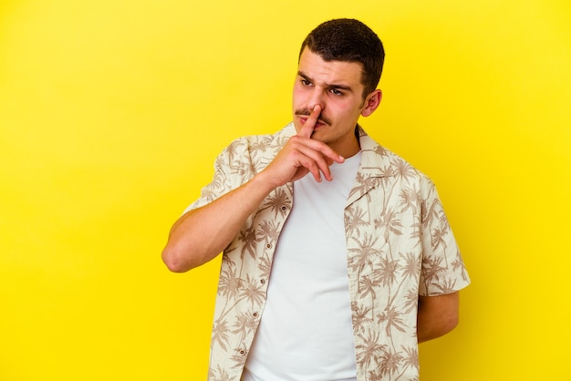 Giovane uomo freddo isolato sulla parete gialla mantenendo un segreto o chiedendo silenzio